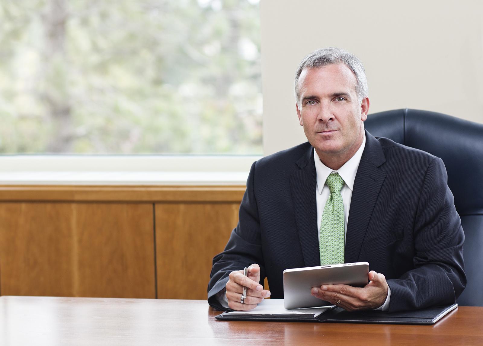 bigstock-Mature-Businessman-using-table-56107859
